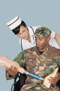 Nurse with us marine corps soldier holding artificial limb as he sits in wheelchair over light blue background Royalty Free Stock Photography