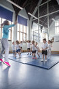 Nursery pe class physical education lesson with students they are doing star jumps with their teacher Stock Photos
