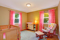 Nursery room with pink ruffle curtains cozy bright furnished dresser comfortable armchair and crib Stock Photo