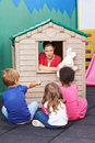 Nursery teacher using playhouse for theater play with stuffed animals children Royalty Free Stock Image