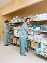 Nurses arranging stock on shelves in storage room full length of male and female hospital Stock Photos