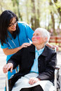 Nursing home beautiful doctor nurse in blue coat walking a kind elderly lady in wheelchair in park Royalty Free Stock Photo