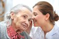 Nursing home female nurse is speaking in senior women ear Stock Photo