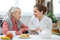 Nursing home senior women eats lunch at retirement Royalty Free Stock Photos