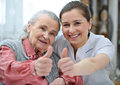 Nursing home senior women and female nurse are showing thumbs up Royalty Free Stock Images