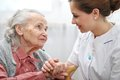Nursing home senior women with her caregiver at Stock Photography