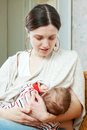 Nursing three month baby over home interior background Stock Photo
