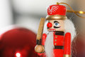 The nutcracker traditional wooden in front of red christmas balls Stock Image