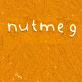 Nutmeg abstract background made of powder with text Stock Photo