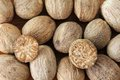 Nutmeg seeds cut in half on a wooden background Royalty Free Stock Photos