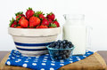 Nutritional breakfast of fruit and milk with bowls full strawberries blueberries a pitcher wholesome Royalty Free Stock Photos