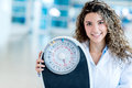 Nutritionist at the hospital female holding a weight scale Royalty Free Stock Image