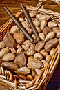 Nuts assortment in wicker basket with nutcracker of a almonds and walnuts and hazelnuts and chestnuts and pecans and nutmegs an Stock Images