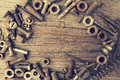 Nuts, bolts and screws on a shabby wooden background. Royalty Free Stock Photo