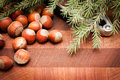 Nuts and nutcracker on wooden background with christmas tree Stock Photos