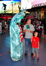 Nyc statue of liberty mime in times square a towering dressed as the poses for photos with two tourists the heart s Royalty Free Stock Images
