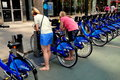 Nyc woman using citibikes at docking station two young women removing their rented from a on broadway th street in Stock Photo