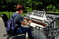 Nyc young man playing piano in central park korean tries out one of the play me pianos this one on cherry hill s part of a summer Royalty Free Stock Photo