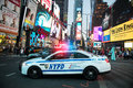 NYPD police squad car goes to emergency call with alarm and siren light in the Time Square streets of New York City, New York, Uni Royalty Free Stock Photo