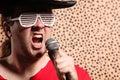 O cantor louco com um chapéu negro grande vidros da rocha e do rolo do partido na frente de uma chita descasca o fundo Foto de Stock