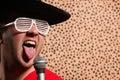 O cantor louco com um chapéu negro grande vidros da rocha e do rolo do partido na frente de uma chita descasca o fundo Imagens de Stock Royalty Free