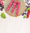 O gelado cor de rosa estala com bagas do verão e o rmint sae no fundo de madeira branco fim acima Imagem de Stock