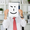 O homem de negócios holding wink smiley in front of his enfrenta Imagens de Stock