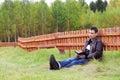 O homem lê o livro na grama perto da cerca de madeira alaranjada Fotografia de Stock