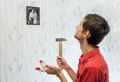 image photo : The young man hung pictures on the wall, improving interior