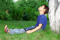 O menino com caderno senta-se na árvore Fotos de Stock