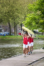 Oarsmen carrying a rowing boat Royalty Free Stock Images