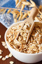 Oat flakes in a bowl witn wooden scoop close up Royalty Free Stock Photos