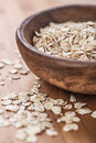 Oat flakes in bowl on wooden table Stock Photos