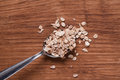 Oat flakes on metal spoon on brown wooden table Royalty Free Stock Photo