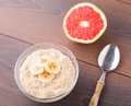 Oat porridge with banana and grapefruit on a table Stock Image