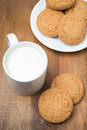 Oatmeal cookies and a mug of milk on a wooden board top view Royalty Free Stock Photos