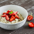 Oatmeal with honey and strawberries in a white bowl on a dark wooden table. Royalty Free Stock Photo