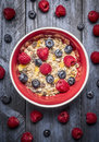 Oatmeal muesli with fresh berries in red bowl on blue rustic backgrund, top view. Sport, health and diet food concept. Royalty Free Stock Photo