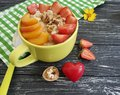 Oatmeal, nuts, strawberry, apricot, delicious heart on a black wooden background Royalty Free Stock Photo
