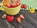 Oatmeal, nuts, strawberry, apricot,organic delicious heart on a black wooden background Royalty Free Stock Photo