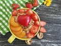 Oatmeal, nuts, strawberry, apricot,organic snack delicious heart on a black wooden background Royalty Free Stock Photo