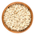Oatmeal, rolled oats in wooden bowl over white Royalty Free Stock Photo