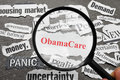 Obama care headline magnifying glass looking at newspaper headlines with obamacare in red Royalty Free Stock Images