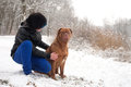 Obedience dog and his owner funky boy is having fun with in the snow Royalty Free Stock Photo