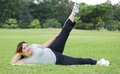 Obese women exercise woman side scissor kick on grass Stock Images