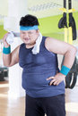 Obesity person wiping his sweat at gym overweight smiling the camera while with a towel fitness center Royalty Free Stock Images