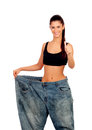 Objective achieved woman at her ideal weight slim with huge pants isolated on white background Stock Photography