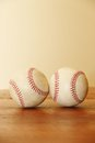 Objects two baseballs on wood table sitting next to each other a wooden one is sideways and they are touching Royalty Free Stock Photography