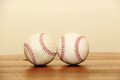 Objects two baseballs on wood table sitting next to each other a wooden one is sideways and they are touching Stock Image