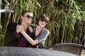 Occhiali da sole da portare delle giovani coppie felici sul patio Fotografia Stock